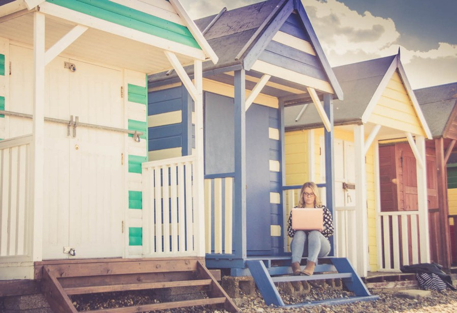 Paula sitting on beach huts with laptop.jpg